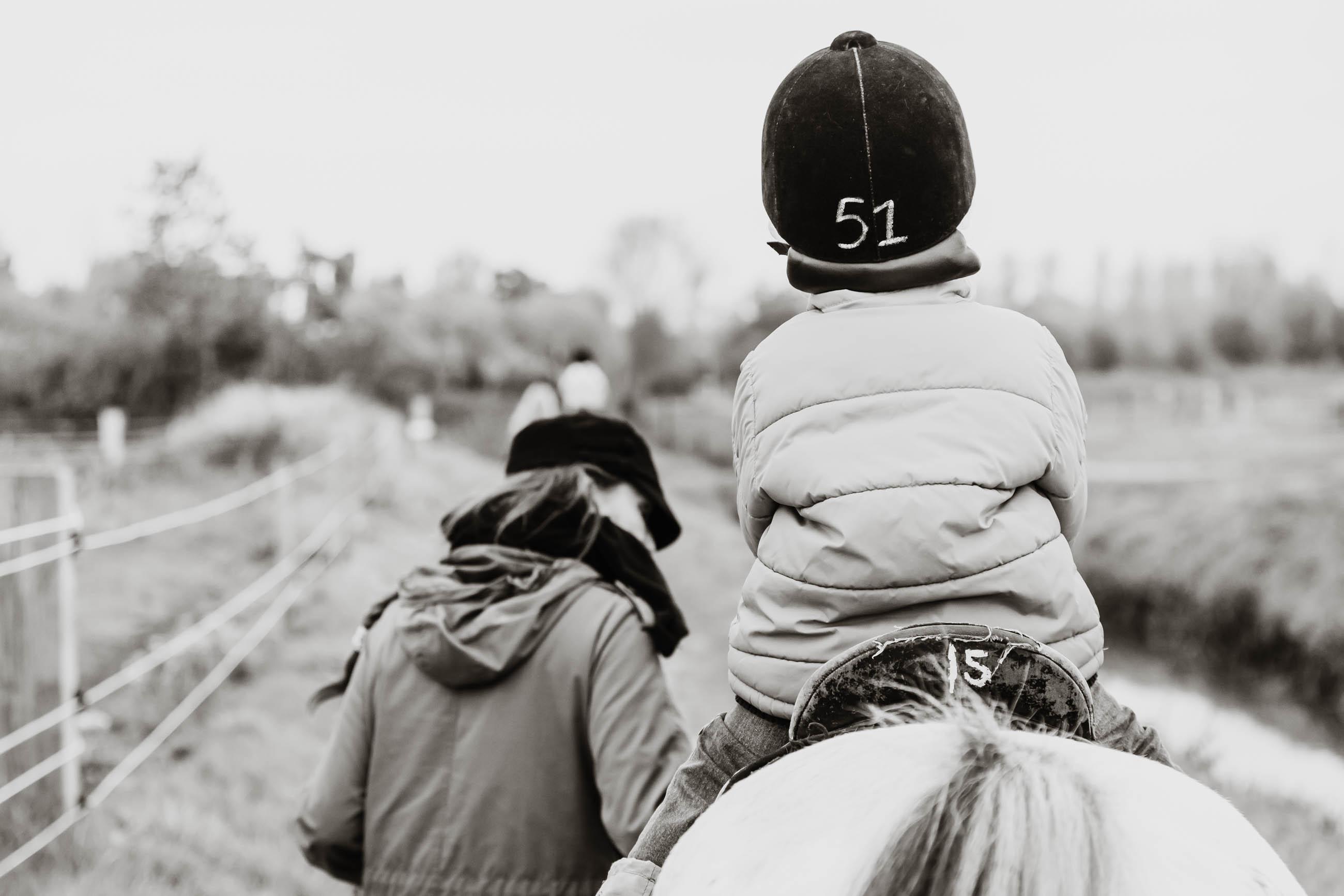 EIN KINDER SITZT AUF EINEM PFERD UND WIRD VON EINER FRAU GEFÜHRT. KINDERHOTEL FAMILOTEL. FOTOGRAFIERT VON FOTOGRAF SVEN VOGEL AUS KÖLN