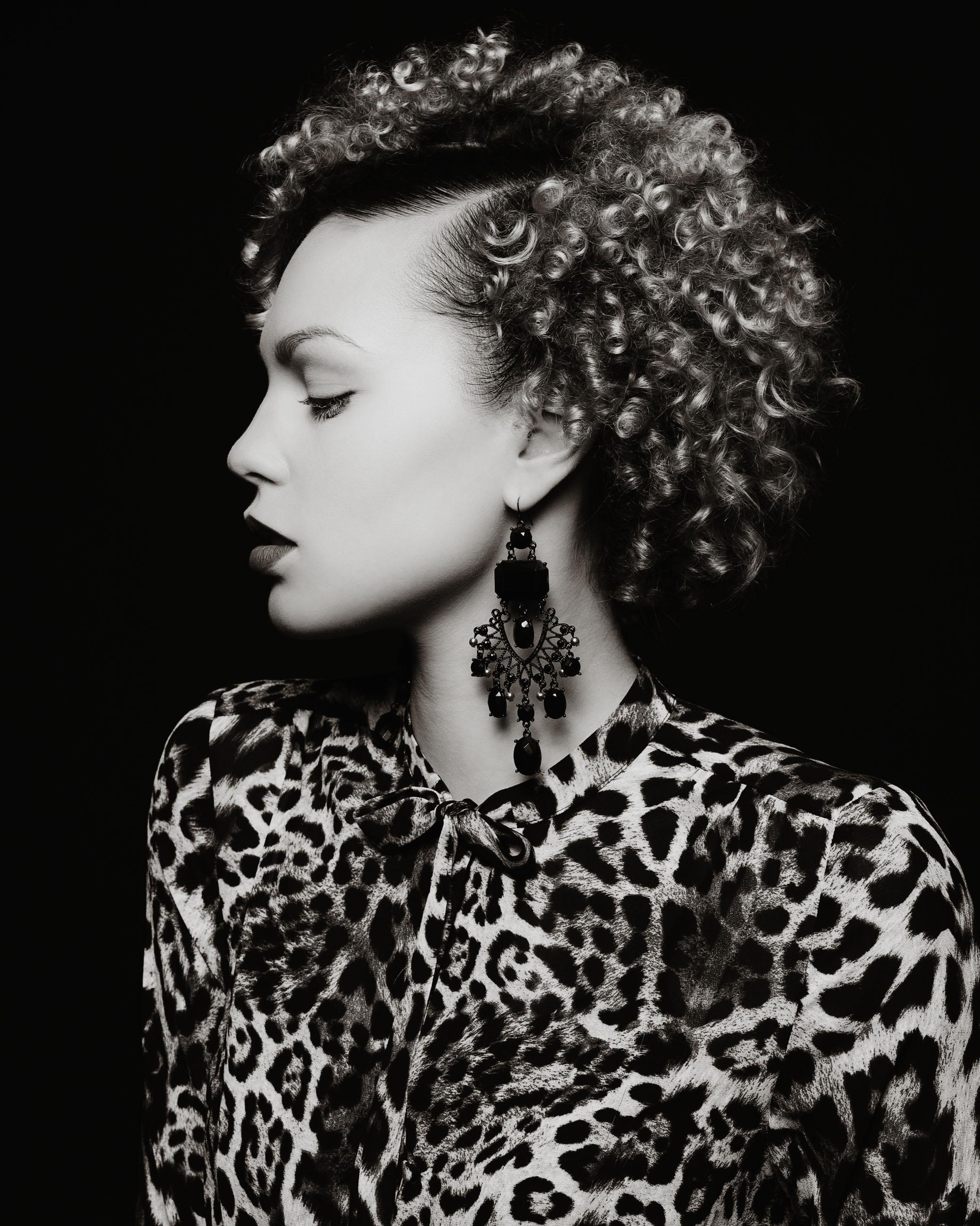 Frau vor dunklem Hintergrund mit Leoparden Kleid und grossen Ohrringen FOTOGRAF Sven Vogel FotografIE lockige schöne Haare Makeup dunkler Lippenstift Schwarz weiß
