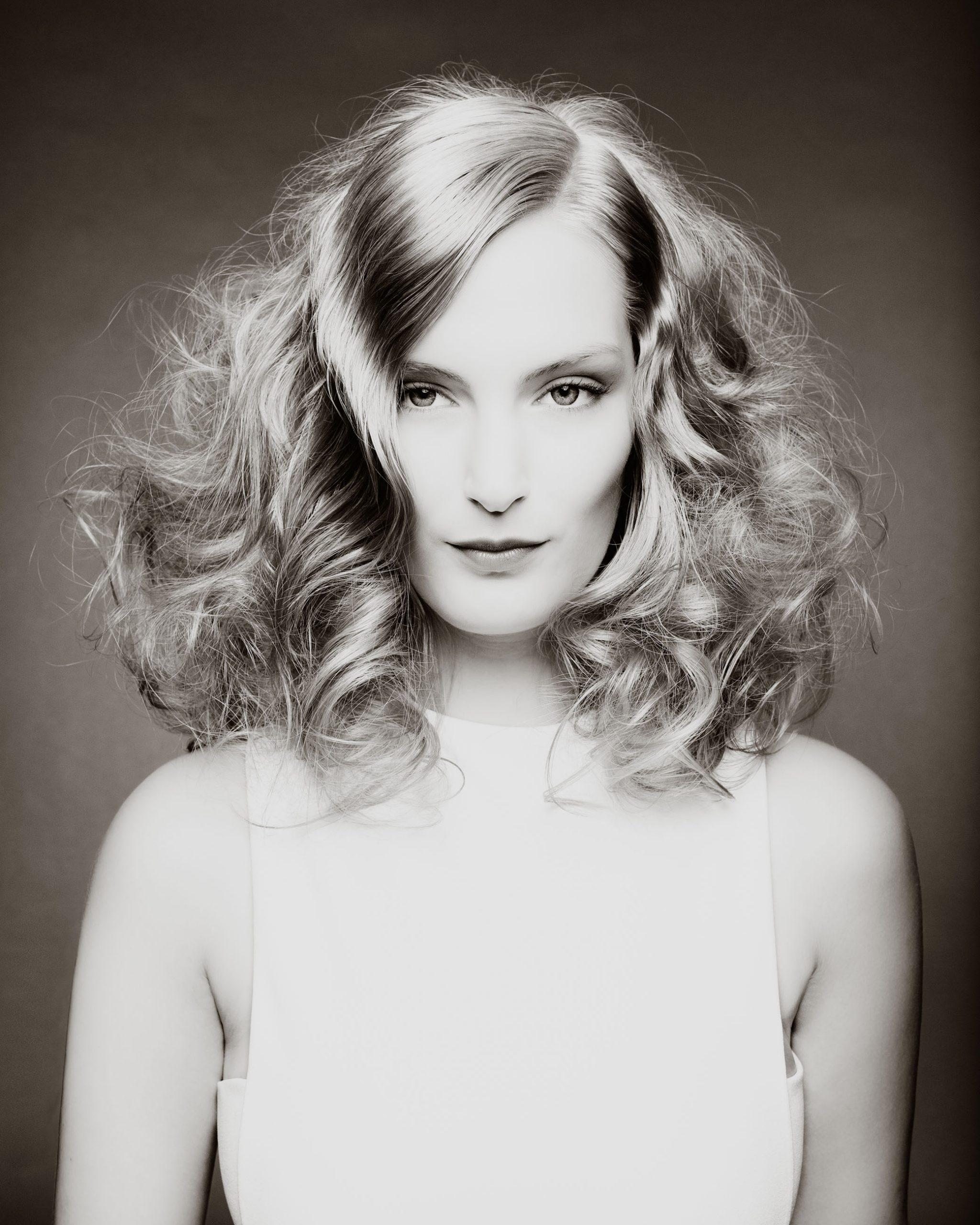 Portrait Blonde Frau mit lockigen Haaren und hellem Makeup vor grauem Hintergrund Schwarz Weiß Sven Vogel Photograph Fotograf