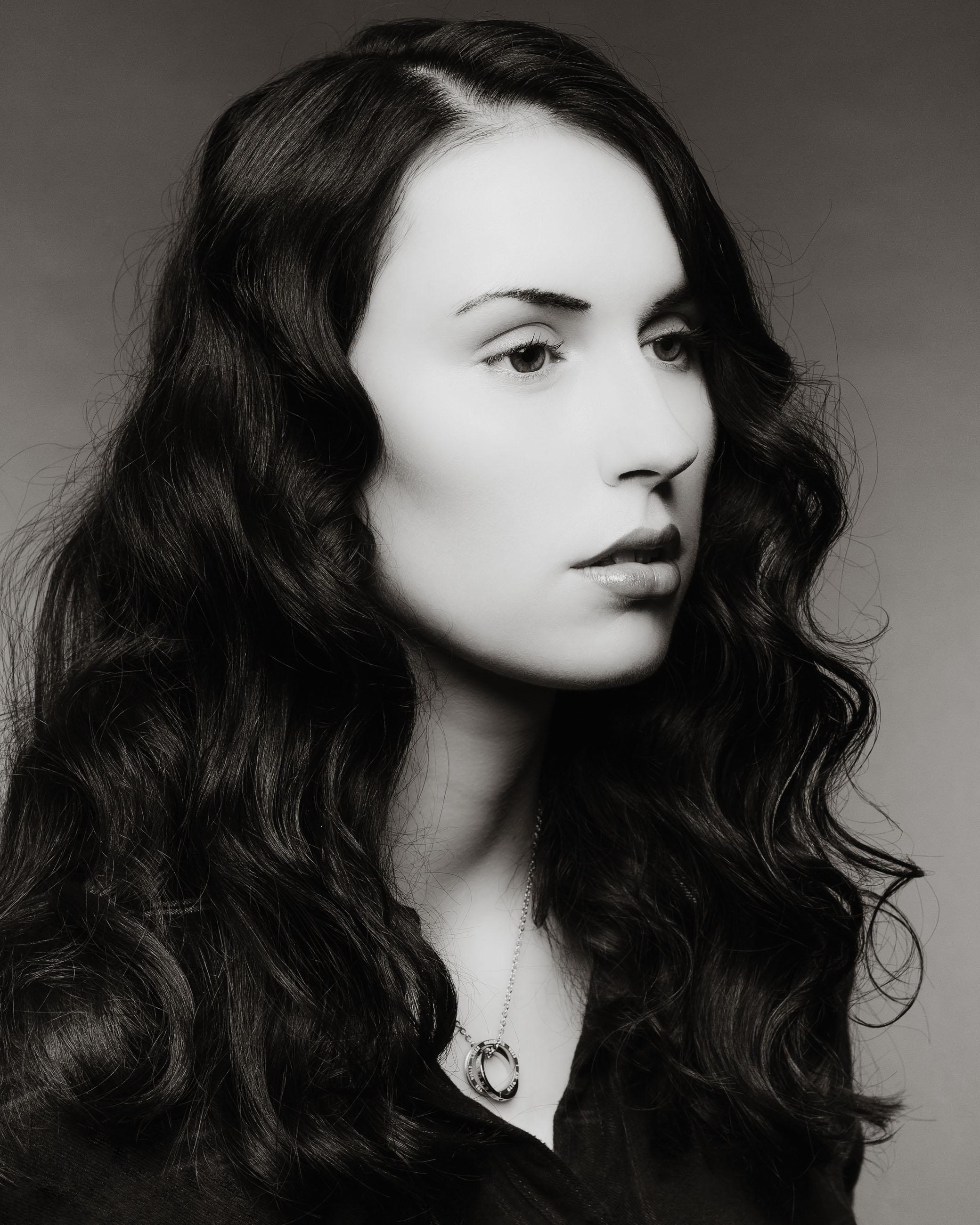 Frau mit dunklen lockigen Haaren vor grauem Hintergrund FOTOGRAF Sven Vogel Photograph Fotografie Schwarz Weiss Foto